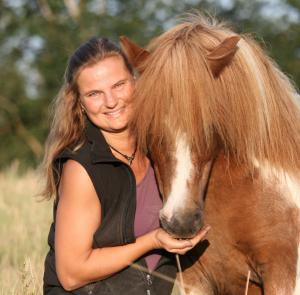 Eine Frau schmust mit einem braun-weißen Pony.