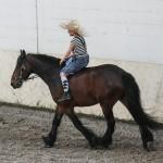 Eine Reiterin parodiert zu Pferd das heutige Reiten.