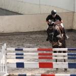 Ein Reiter springt mit Pferd über einen Steilsprung.